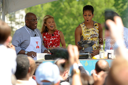 First Lady Michelle Obama flips a crepe at a cooking station as Al Roker and Kelly Ripa look on during the White House Easter Egg Roll on the South Lawn of the White House in Washington, DC, on Monday, April 25, 2011.  .Credit: Roger L. Wollenberg / Pool via CNP