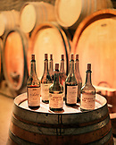 FRANCE, FRANCE, Montigny-les-Arsures, Arbois, bottles of Vin Jaune sit on a wine barrel, Jacques Puffeney Winery, Jura Wine Region
