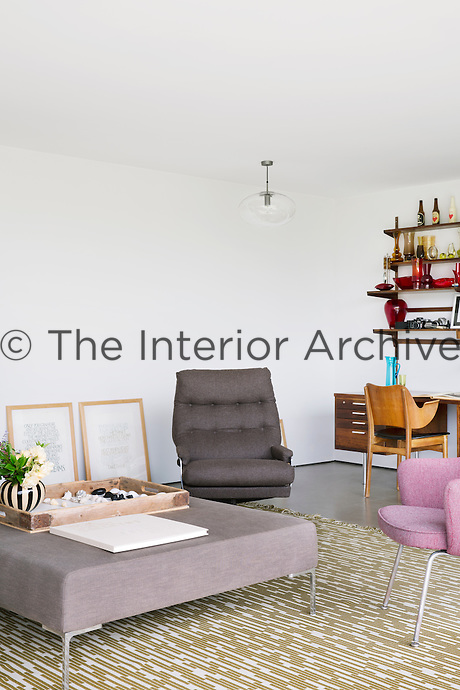 The sitting room is furnished in a minimalist style with a mixture of mid-century and contemporary pieces, such as a vintage Arne Jacobsen rug and an ottoman from B&B Italia. The plywood armchairs are vintage pieces by Thonet and desk is Scandinavian mid-century.