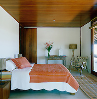 This simple guest bedroom has a wooden tongue and groove ceiling and comfortable double bed