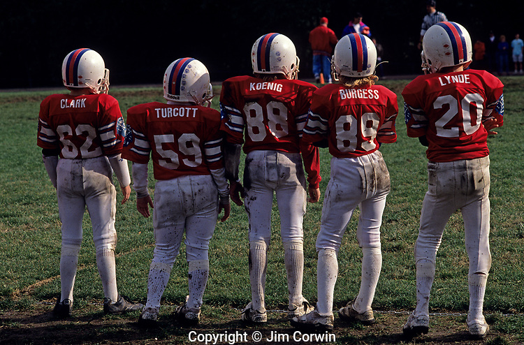 Football team along sidelines during game with backs to camera waiting to go in