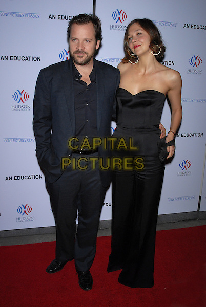 """PETER SARSGAARD & MAGGIE GYLLENHAAL.New York Premiere of """"An Education"""" held at The Paris Theater, New York, NY, USA..October 5th, 2009.full length black strapless top trousers jumpsuit catsuit blue suit hand in pocket married husband wife beard facial hair .CAP/LNC/TOM.©TOM/LNC/Capital Pictures."""