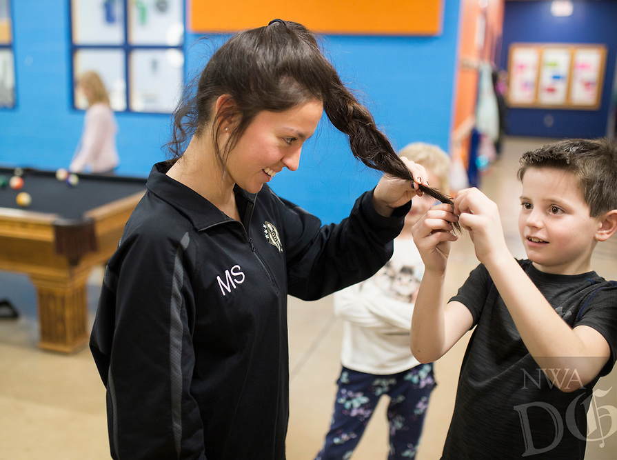 NWA Democrat-Gazette/CHARLIE KAIJO Gabriel Browder, 9, of Centerton (right) learns how to tie a braid as staff member Megan Sattler of Bentonville (left) reacts, Monday, January 7, 2019 at the Boys and Girls Club in Bentonville. <br />