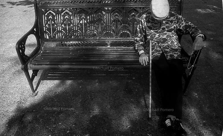 01.2010 Santiago de chile (Chile)<br /> <br /> Homme en train de dormir sur un banc public avec son chapelet  dans sa main.<br /> <br /> Man sleeping on a park bench with his rosary in his hand.