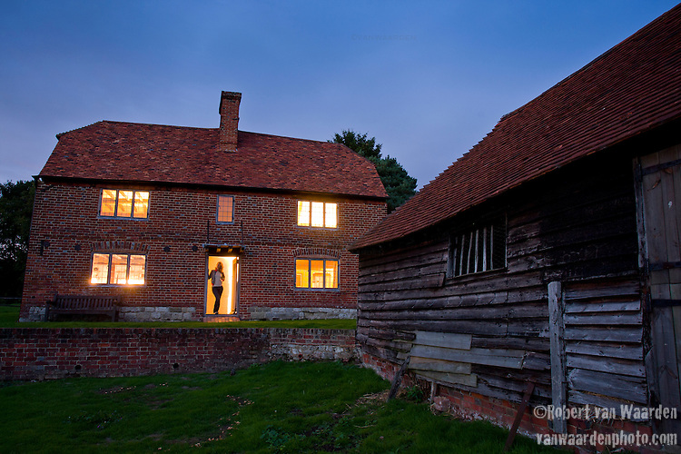 A woman stands in the doorway of Obriss Farm at dusk. Obriss Farm is a building near Westerham, Kent,  belonging to the Landmark Trust, a United Kingdom building preservation charity that rescues historic buildings at risk and gives them a new life as places to stay in and experience.