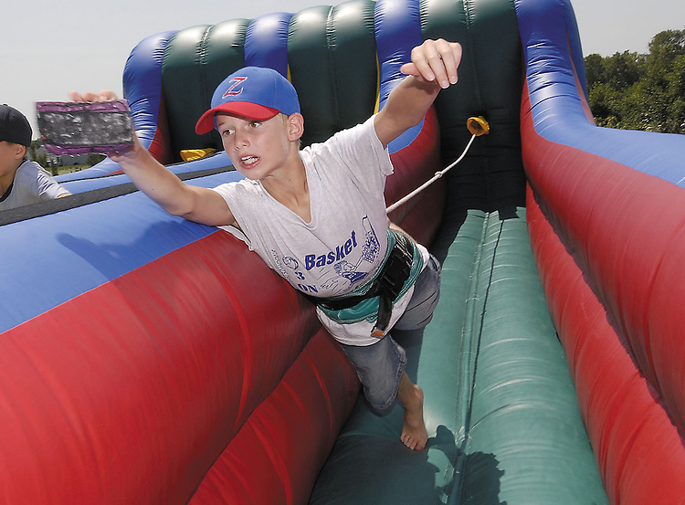 """Sentinel/Dan Irving.Zeeland Christian School fifth-grader Johnathan Admiraal dives forward against a bungee cord during the """"Caring 4 Karl"""" event Saturday afternoon near Zeeland East High School.  The event was a fundraiser for local little league coach Karl Elzinga, who is fighting cancer. .(7/29/06)"""