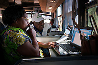 Fulgence Ndikubwimana helps fellow trainee during computer class on ICT bus Kabaya, Rwanda. (Photo by Tadej Znidarcic)