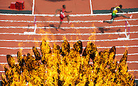 03.08.2012 Stratford, England. A view of the Olympic Flame within the stadium as heat 2 Mens 400m Hurdle competitors come past on track on day 7 of the London 2012 Olympic Games in the Olympic Stadium on the Olympic Park.