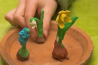 Kinder basteln Frühjahrsblumen aus Knete, Bastelei, Kind stellt fertiges Schneeglöckchen zu Hyazinthe und Narzisse, Osterglocke auf Tonteller