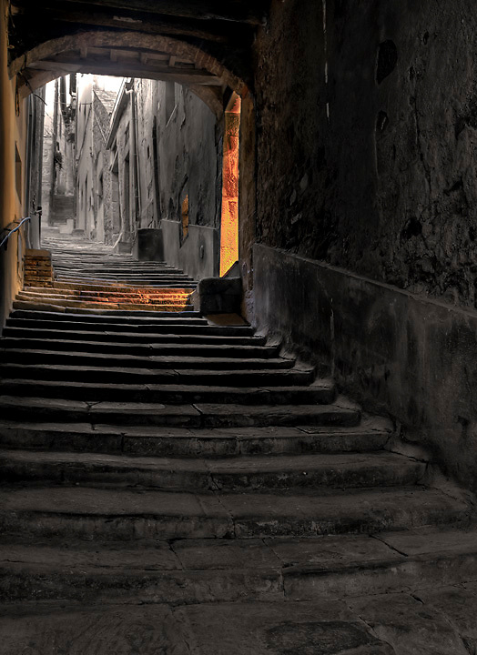 Photograph of a dark stairway in Cortona leading up past an open door that floods the steps with light.