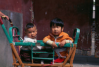 China, Peking, Kinder in traditionellem Kinderwagen.