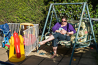 A mother breastfeeds her baby while sitting in her garden swing seat.<br /> <br /> Taken - 27/04/2011<br /> Hampshire, England, UK