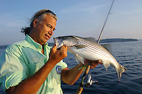 Angler with striped bass caught in Lake Ouachita, Arkansas