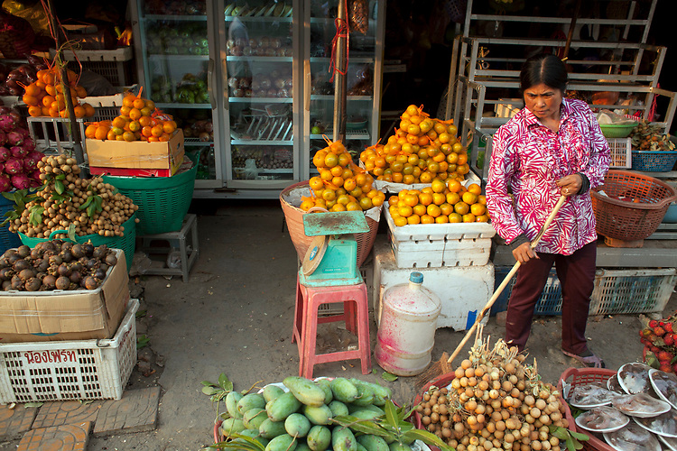 A Cambodian woman cleans up her fruit and vegetable stall at a marketplace in Phnom Penh, Cambodia. <br /> <br /> Photos &copy; Dennis Drenner 2013.