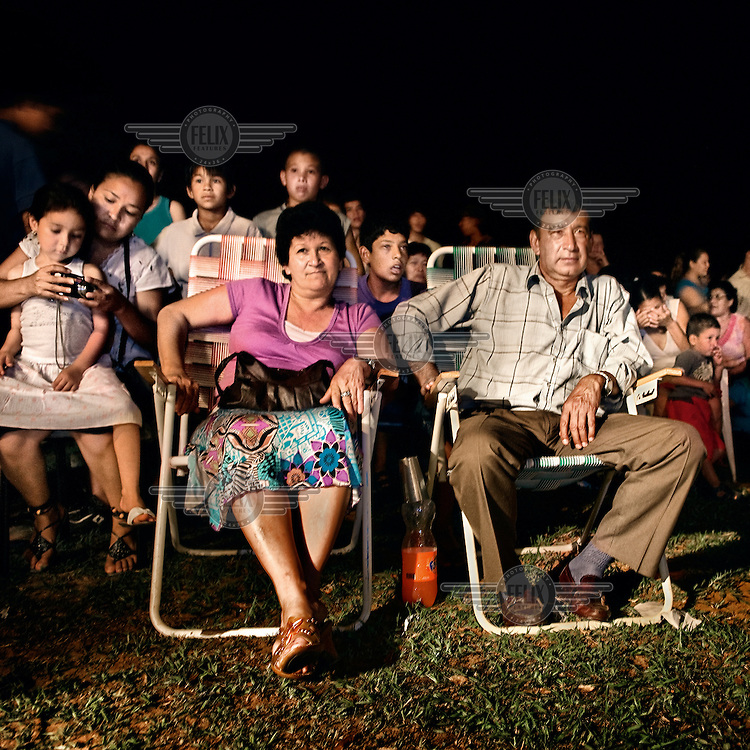 People on Itape island in the Parana River watch a performance by a group of musicians.