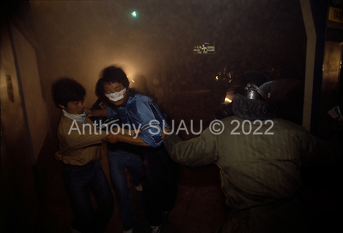 Kwanju, South Korea<br /> May 1987<br /> <br /> Plain-clothed policeman acts in unison with riot police to arrest a student demonstrator.<br /> <br /> After two decades of building an economic miracle, in the summer of 1987 tens of thousands of frustrated South Korean students took to the streets demanding democratic reform. &quot;People Power&quot; Korean-style saw Koreans from all social spectrums join in the protests.<br /> <br /> With the Olympics to be held in South Korea in 1988, President Chun Doo Hwan decided on no political reforms and to choose the ruling party chairman, Roh Tae Woo, as his heir. The protests multiplied and after 3 weeks Chun conceded releasing oppositionist Kim Dae Jung from his 55th house arrest and shaking hands with opposition leader Kim Young Sam. Days later he endorsed presidential elections and an amnesty for nearly 3,000 political prisoners. It marked the first genuine initiative of democratic reform in South Korea and the people had their victory.