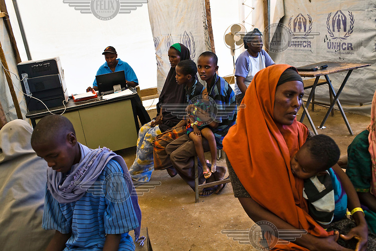 Somali refugees wait to be registered onto the database at the IFO camp, part of the Dadaab refugee camp in Kenya. The drought is the worst in East Africa for 60 years. The UN described it as a humanitarian emergency. The already overcrowded complex received 1,000 new refugees a day in June, five times more than a year ago. About 30,000 people arrived at the Dadaab refugee camp in June, according to UNHCR compared to 6,000 in June 2010.