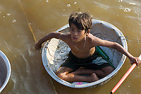 A domestic tin basin has been turned into a make-shift boat by this boy so that hecan get around hisfloating village on Tonle Sap Lake in Cambodia. He can not always do this since Tonle Sap Lake swells to cover ten thousand square kilometres at the end of the rainy season and tropical storms can blow up quickly.