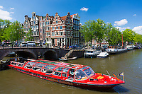 Tourist boat takes tour cruise group sightseeing on Dutch canals, Prinsengracht and Brouwersgracht, Amsterdam, Holland