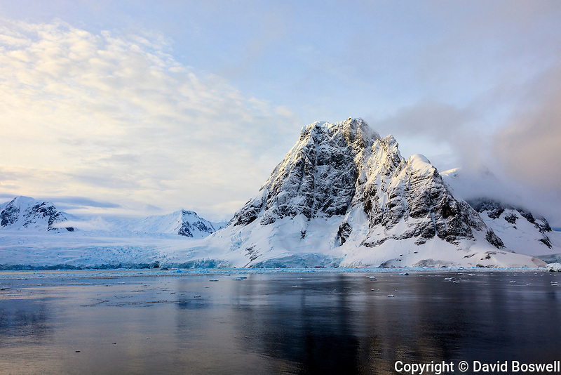 Small peaks, cliffs, and ice abound along the Lemaire Channel offshore of the Antarctic Peninsula.