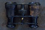 Used pair of opera glasses or binoculars lying on rusty metal sheet