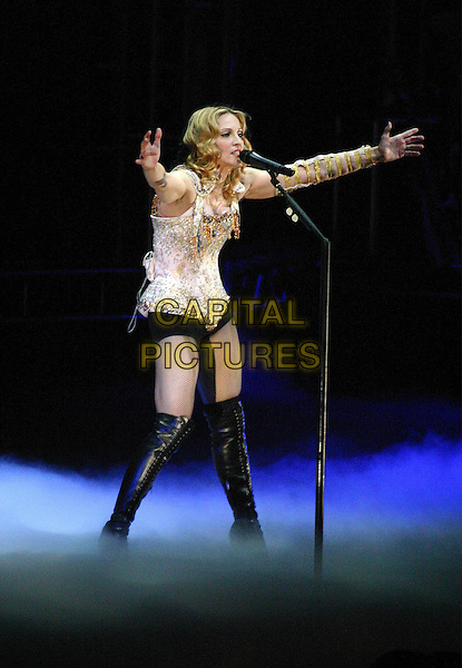 "MADONNA.On her ""Re-Invention"" tour performs live in concert at Madison Square Garden, New York,USA,.23rd June 2004..full length gig music on stage black hotpants long over the knee boots gold beaded bodice corset top fishnet tights.www.capitalpictures.com.sales@capitalpictures.com.©Capital Pictures"