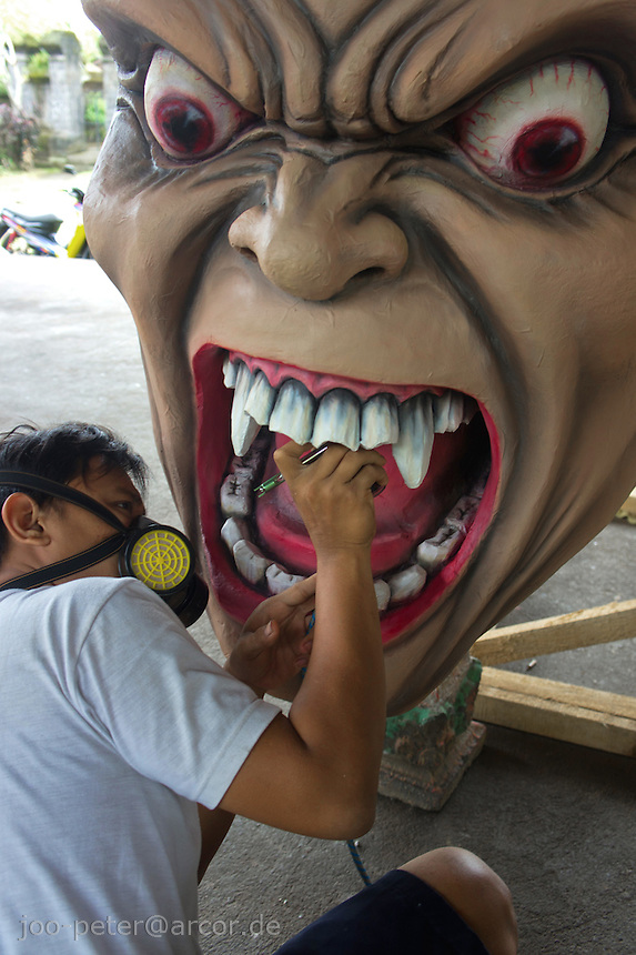 artist Epong paints teeth of a Ogoh-ogoh  called  Bhuta Kala (demon spirit),  Kala Tetajen (spirit of gambling and cockfight), Pelihatan,Central Bali, 2012. The head will be placed on the huge body sculpture one day later.. Balinese New Year called Nyepi (around march according to lunar calendar),  is a silent day of meditation and spiritual purification. One day before exorcist rituals are held for purification and balance of polar powers of the universe, first at noon by a priest (exorcism called Caru or Tawur Agung) and later on after sunset in a popular, carneval-like procession of Ogoh-Ogoh, symbolizing bhuta kali (demon, bad spirits,bad habits),  so all the bad spirits leave the village and the island.  Loud, rhythmic music and special performances are part of the procession called Ngerupuk. Road crossings are major spots of exorcism and special ogoh-ogoh performance, since demons often like to dwell here. At Nyepi, the following day, there is 24 hours silence, no vehicle or people on the street, no light or fire, no working - all the bad spirits should think, the island is abandoned and leave the island. Day after Nyepi is a day of reconciliation - new year starts purified.