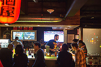 People sit at the bar at Hojoko, a Japanese bar and restaurant in The Verb Hotel in the Fenway neighborhood of Boston, Massachusetts, USA, on Friday, Dec. 4, 2015.