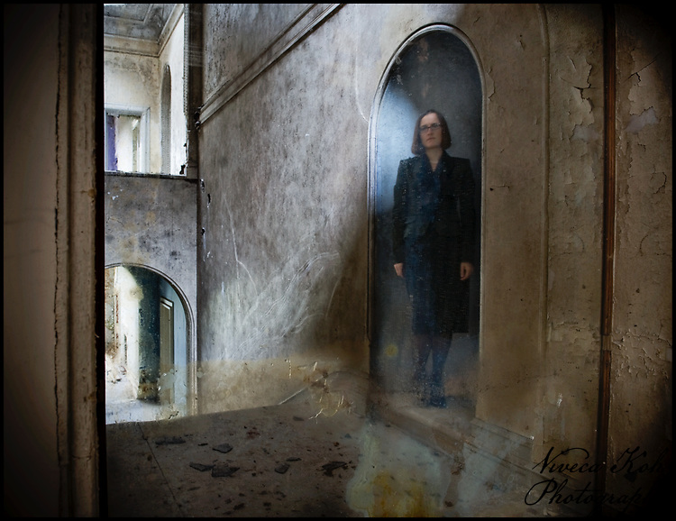 Miss V in an archway, trapped inside the mirror