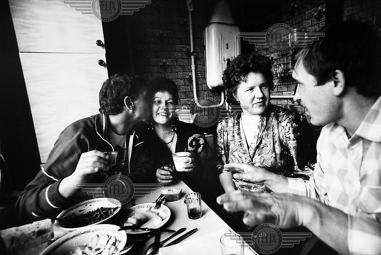 Two couples sitting in a kitchen drinking homemade vodka and eating.