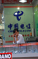 A sales assistant at a China Telecom shop sells mobile phones..