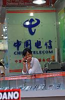 A sales assistant at a China Telecom shop sells mobile phones..