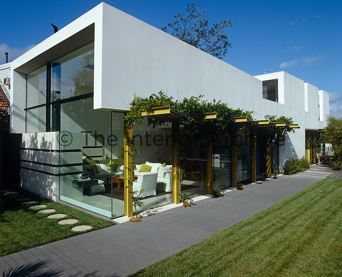 Large picture windows connect the modern  living space with the garden