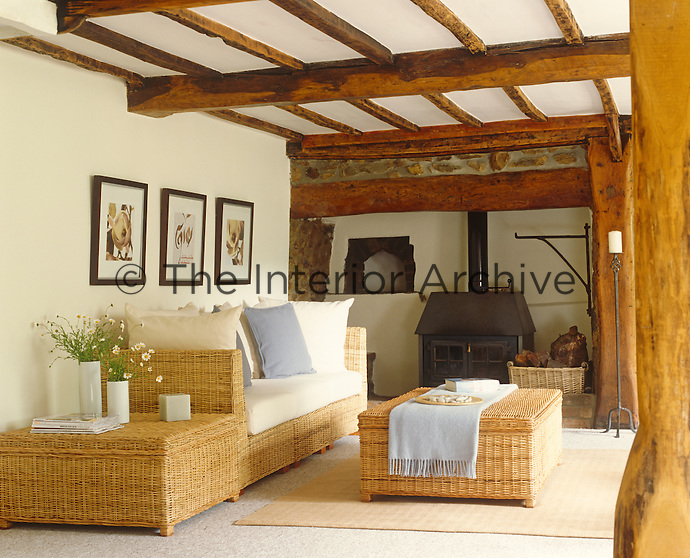Old and new combine in the living room of this traditional country cottage with its contemporary wicker furniture and exposed beams