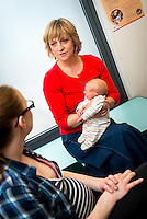 "Part of a series of photos in which a midwife listens to the difficulties a young woman has with breastfeeding her baby, finds that the baby has a tongue-tie, performs a tongue-tie division, helps the mother achieve a better latch and then gives the final bits of advice while doing her paper work.<br /> <br /> Image from the breastfeeding collection of the ""We Do It In Public"" documentary photography picture library project: <br />  www.breastfeedinginpublic.co.uk<br /> <br /> Hampshire, England, UK<br /> 13/03/2013<br /> <br /> © Paul Carter / wdiip.co.uk"