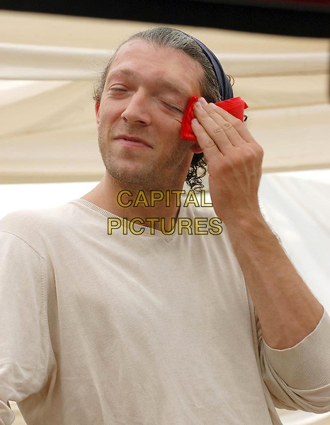 """VINCENT CASSEL.Photocall for the movie """"Blueberry"""".Rome, Italy, 28th june 2005..half length hairband hair band funny wiping sweat sweaty red tissue hankerchief face.Ref: OME.www.capitalpictures.com.sales@capitalpictures.com.©Omega/Capital Pictures."""