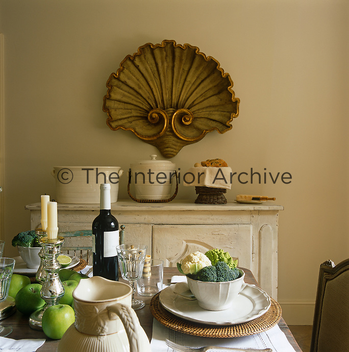 An antique gilded, carved wooden shell hangs on the kitchen wall where the table has been laid with white Provençal china pieces paired with rattan chargers by Nicholas Haslam