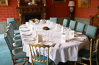 The luxurious classic old-fashioned dining room set for a gala dinner with starched napkins and white table cloth and many glasses for tasting the champagnes as seen through the entrance door roses decorating the table and menus at Champagne Deutz in Ay, Vallee de la Marne, Champagne, Marne, Ardennes, France, low light grainy grain