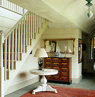 A small circular table and antique chest of drawers have been placed beneath the stairs in the main hall