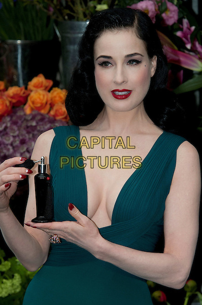 Dita Von Teese .Dita Von Teese, the burlesque superstar, appeared at Liberty London to launch her debut fragrance, named after herself, London, England..May 1st, 2012.perfume half length dress low cut neckline cleavage red lipstick teal blue green bottle.CAP/BF.©Bob Fidgeon/Capital Pictures.