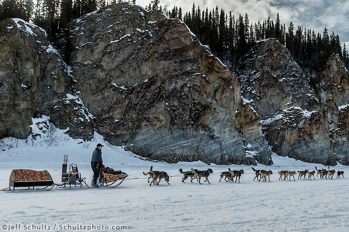 Jeff King runs past cliffs on the Yukon River shortly after leaving the Ruby Checkpoint during the 2016 Iditarod.  March 11, 2016   <br /> <br /> Photo by Jeff Schultz (C) 2016  ALL RIGHTS RESERVED