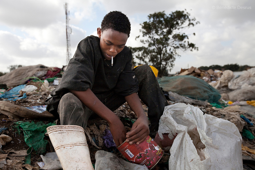 13 february 2013 - Dandora dumpsite, Nairobi, Kenya - A young Kenyan scavenger dig for items to sell and food waste to eat at the Dandora dumpsite, one of the largest and most toxic in Africa. Located near slums in the east of the Kenyan capital Nairobi, the open dump site was created in 1975 and covers 30 acres. The site receives 2,000 tonnes of unfiltered garbage daily, including hazardous chemical and hospital wastes. It is a source of survival for many people living in the surrounding slums, however it also harms children and adults' health in the area and pollutes the Kenyan capital. Photo credit: Benedicte Desrus