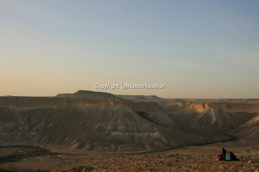 Israel, Northern Negev Mountain. Campers on the cliff overlooking Zin valley