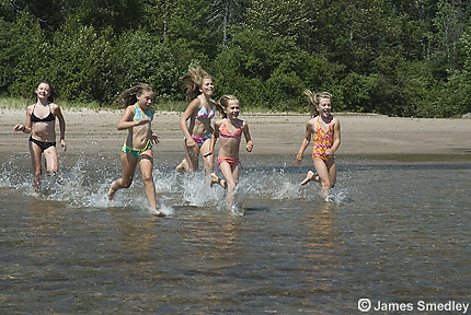 Young girls in bathing suits running in the waves at the beach
