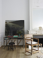 A simple Italian wooden chair is part of the eclectic mix of furniture and objects in the living room