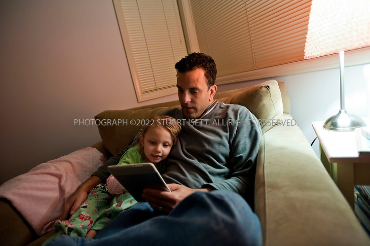 10/13/2009--Woodinville, WA, USA..Brandon Watson at home reading a bed time story from his Amazon Kindle to his 4 yr. old daughter, Casseia. Mr. Watson went from reading one book a month to several since he got his Kindle...©2009 Stuart Isett. All rights reserved.