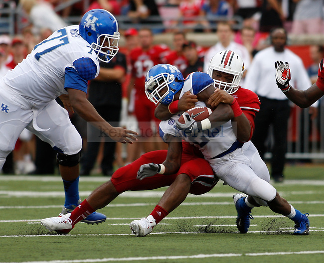 UK senior tailback CoShik Williams is tackled during the first half of the UK vs. UL football game at Papa John's Cardinal Stadium in Louisville, Ky., on Sunday, September 2, 2012. Photo by Tessa Lighty | Staff