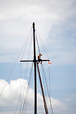 INDONESIA, Mentawai Islands, Kandui Resort, man sitting on sailboat mast photographing the surfers