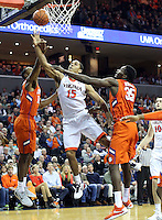 Virginia guard Malcolm Brogdon (15) shoots between Clemson forward Donte Grantham (15) and Clemson center Landry Nnoko (35) during an ACC basketball game Tuesday Jan. 19, 2016, in Charlottesville, Va. Virginia  defeated Clemson  69-62. (Photo/Andrew Shurtleff)