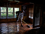 MASHES SANDS BEACH, FL - OCTOBER 11: Royal Baker sweeps the muddy sludge from the storm surge from Hurricane Michael out his front door on October 11, 2018 in Mashes Sands Beach, Florida. Baker had raised some of her furniture off the floor in anticipation of the storm surge.  (Photo by Mark Wallheiser/Getty Images)